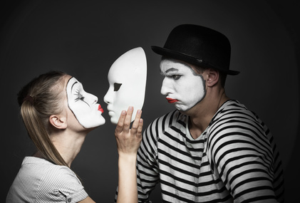 Female mime kissing the mask of male mime